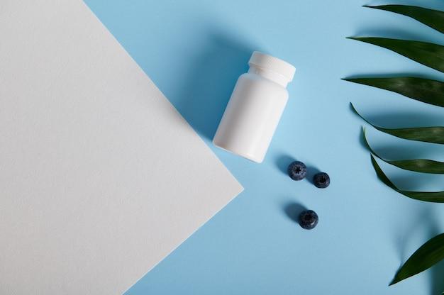 Flache lage eines weißen pillenbehälters und verstreuter blaubeeren in der nähe von palmblättern