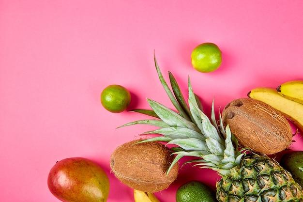 Flache lage exotischer früchte auf rosafarbenem hintergrund - mango, ananas, banane, avocado, kokosnuss, limette. ansicht von oben. kreatives layout aus tropischen früchten, kopierraum, sommerkonzept.