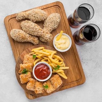 Flache lage gebratener hähnchenschenkel und nuggets mit kohlensäurehaltigen getränken und pommes frites