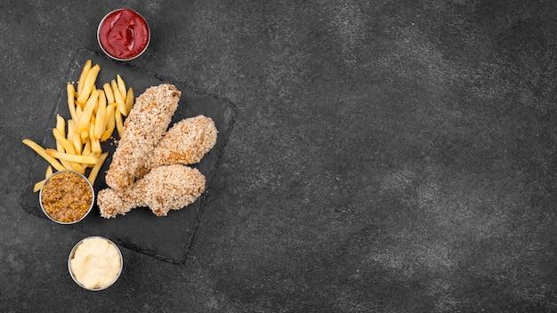 Flache lage gebratenes huhn mit pommes frites und saucen