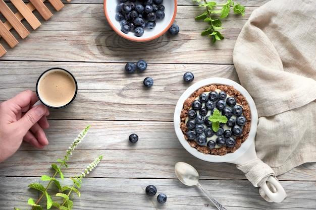 Flache lage köstlicher blaubeertörtchen mit vanillepudding und hand mit kaffee