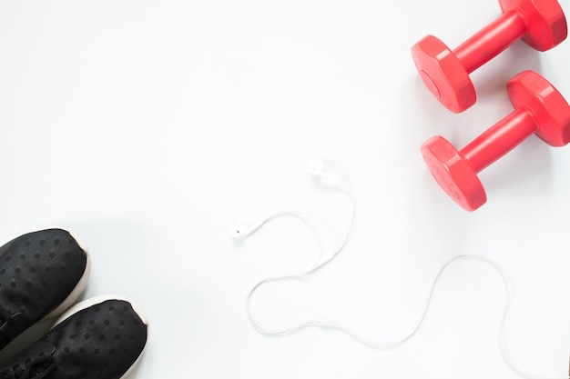 Flache lage kopfhörer, rote hanteln und sportgeräte auf weißem hintergrund. sportbekleidung, sportartikel, sportartikel, sportausrüstung, draufsicht