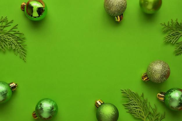 Flache lage, minimaler zusammensetzungshintergrund der draufsicht von grünen dekorativen weihnachtsverzierungen.