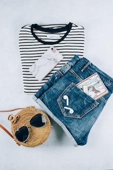 Flache lage mit damenbekleidung und accessoires. gestreiftes t-shirt, shorts, modische rattantasche.