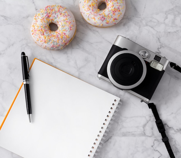 Flache lage mit donuts, blumen, kamera und notizblock auf weißem marmor