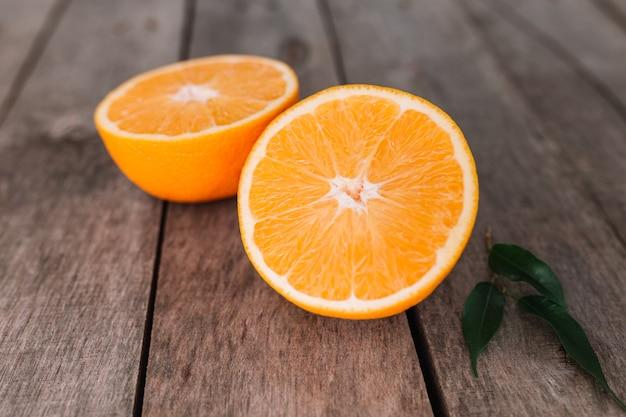 Flache lage mit frisch reifen geschnittenen hälften von orangenfrüchten auf grauem holzhintergrund. orangenfleisch und grüne blätter. tropisches lebensmittelkonzept