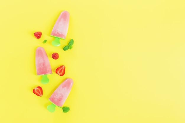 Flache lage mit fruchtigem rosa gefrorenem sorbet-eis auf grüner plastikstocksammlung mit erdbeerschnitten, minzblättern auf gelbem hintergrund. gefrorene gemischte früchte mit joghurt in form von eiscreme