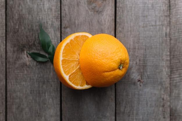 Flache lage mit geschnittenen hälften von frischen und reifen orangenfrüchten auf grauem holzhintergrund