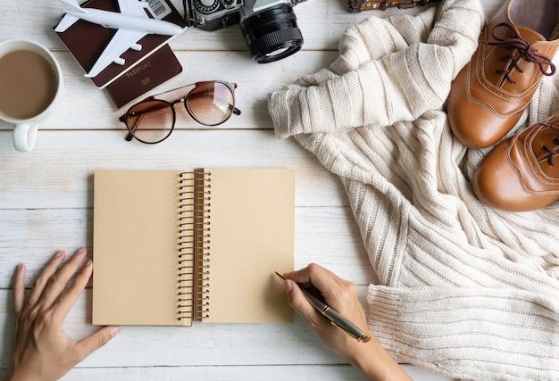 Flache lage mit handschrift auf notebook, bequemes warmes outfit für kaltes wetter, reisezubehör. bequemer herbst, stil im erdfarbenen farbkonzept, draufsicht, kopierraum
