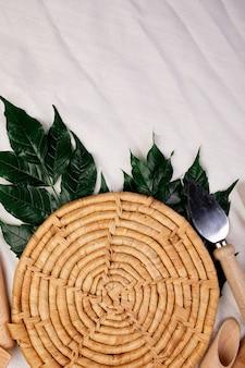 Flache lage mit hölzernen küchenutensilien mit grünen blättern, kochwerkzeugen auf textilhintergrund, von oben erfasste geschirrsammlung, modell, rahmen.