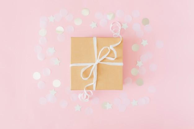 Flache lage mit isolierter geschenkbox aus bastelpapier, gebunden mit konfetti oder glitzern aus band, stern und kreispapier auf rosa pastellhintergrund.