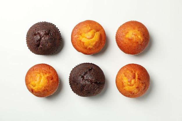 Flache lage mit leckeren muffins auf weißem hintergrund, draufsicht