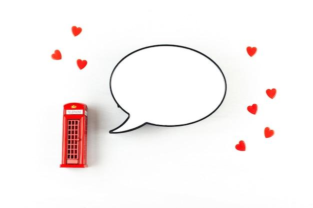 Flache lage mit london-telefonzelle und leuchtkasten in form von spracheblase mit kopienraum für text