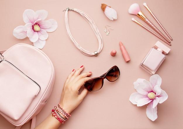 Flache lage mit rosa frauenzubehör mit der rucksack- und frauenhand, welche die sonnenbrille hält. sommermodetrends, einkaufsidee