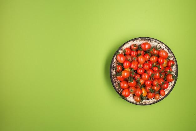 Flache lage mit roten tomaten auf grünem hintergrund.