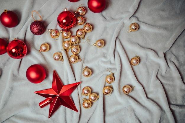 Flache lage mit roten weihnachtskugeln, goldenen weihnachtskugeln und weihnachtszuckerstangen auf dem plaid.