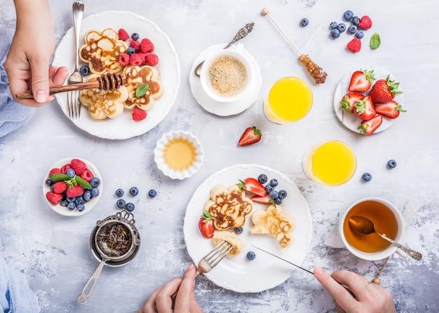 Flache lage mit scotch pancakes in blütenform, beeren und honig mit menschenhänden