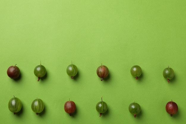 Flache lage mit stachelbeere auf grünem hintergrund