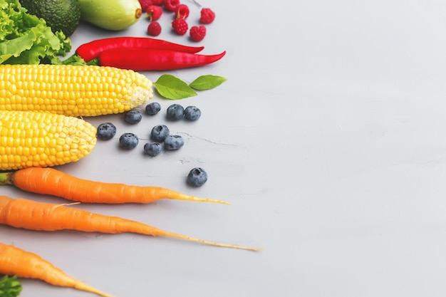Flache lage mit verschiedenem gemüse, obst, beeren, kräutern. kopieren sie den leerraum für etwas text. gemüse auf grauem betonhintergrund. konzept der gesunden ernährung der bio-bionahrung, blaubeere, erdbeere, mais