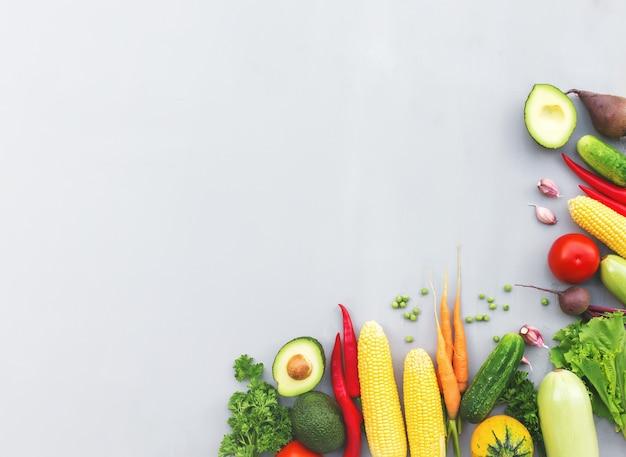 Flache lage mit verschiedenen gemüsen, früchten, beeren, nüssen, gewürzen, kräutern, olivenöl. kopieren sie den leerraum für etwas text. gemüse auf grauem betonhintergrund. konzept der gesunden ernährung mit bio-bio-lebensmitteln