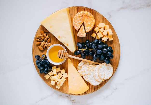 Flache lage mit verschiedenen käsesorten, trauben, nüssen, honig und cracker in holzbrett auf marmor