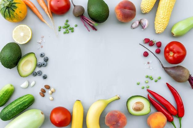 Flache lage mit verschiedenen lebensmitteln, bio-gemüse, bio-früchten, beeren, nüssen, gewürzen, kräutern. kopieren sie den leerraum für etwas text. gemüse auf grauem betonhintergrund. bio-bio-lebensmittel-konzept für gesunde ernährung