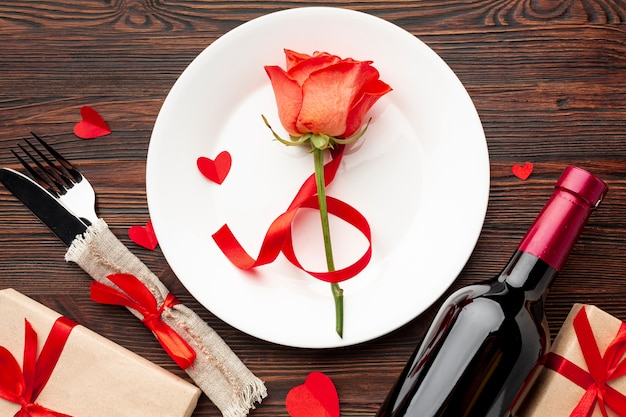 Flache lage reizende anordnung für valentinstagabendessen auf hölzernem hintergrund