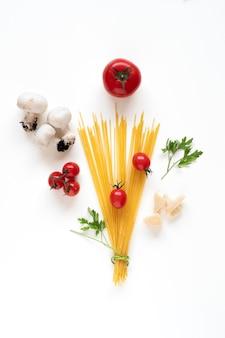 Flache lage roher spaghetti-zutaten, die als blumenstrauß auf weißer oberfläche angeordnet sind