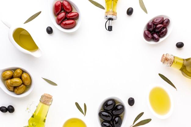 Flache lage rote gelbe schwarze oliven in löffeln mit ölflaschen und kopienraum
