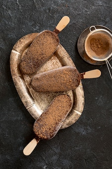 Flache lage schokoladeneis mit kakaopulver und sieb