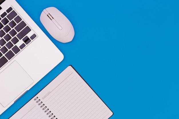 Flache lage schreibtischtabelle des modernen arbeitsplatzes mit laptop auf blauer tabelle