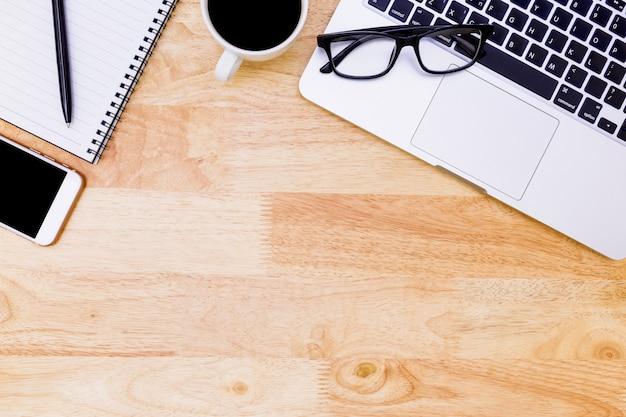 Flache lage schreibtischtabelle des modernen arbeitsplatzes mit laptop auf holz