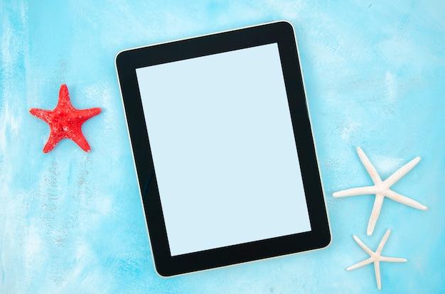Flache lage starfishes und tabletten-pc auf blauem pastellhintergrund