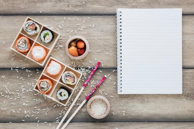 Flache lage sushi-komposition mit notizblock-vorlage