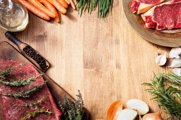 Flache lage verschiedener roher fleisch- und gemüsesorten auf holztisch. essenszubereitung. natürliches eiweiß.