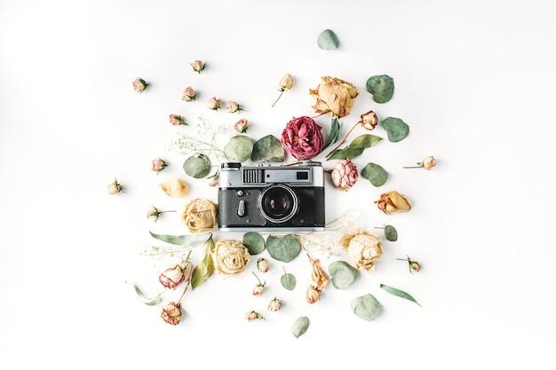Flache lage, vintage-retro-fotokamera der draufsicht, beige rosen und grüne blätter