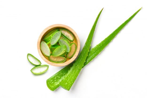 Flache lage von aloe vera in holzschale mit grünen blättern auf weiß isoliert geschnitten.