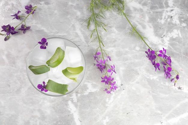 Flache lage von aloe vera-scheiben auf marmorhintergrund