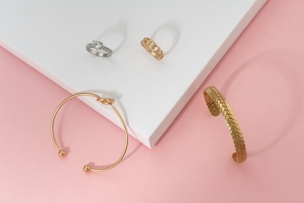 Flache lage von armbändern und ringen in form eines goldenen knotens und eines geflechts