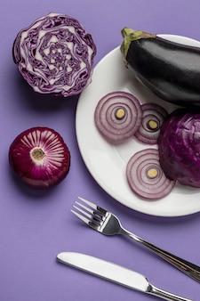 Flache lage von auberginen und zwiebeln auf teller mit besteck