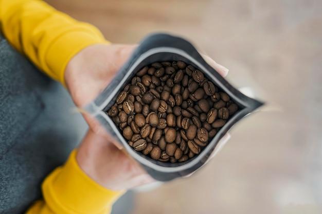 Flache lage von barista, die kaffeepaket hält