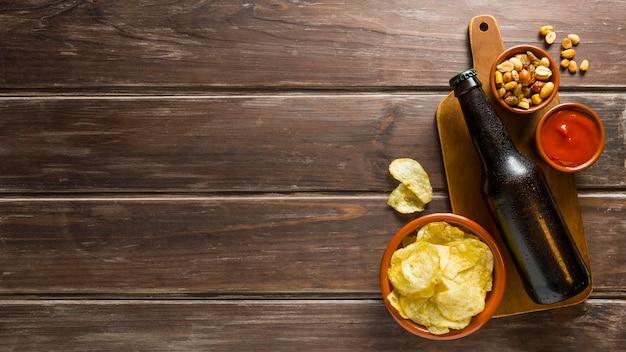 Flache lage von bierflaschen mit pommes und nüssen