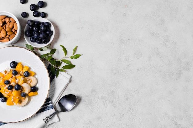 Flache lage von blaubeeren und von mango mit kopienraum