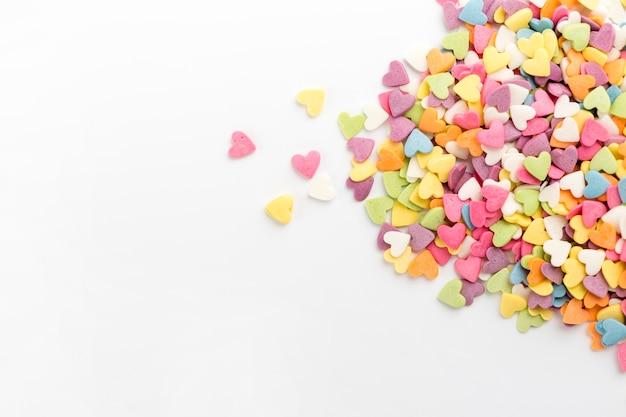 Flache lage von bunten herzförmigen süßigkeiten