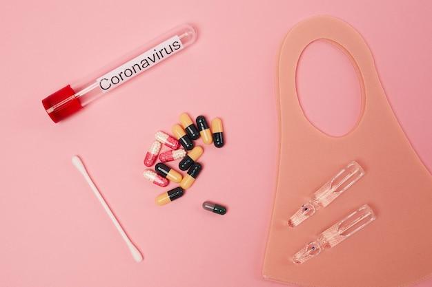 Flache lage von coronavirus-testampulle, pillen und medizin auf rosa