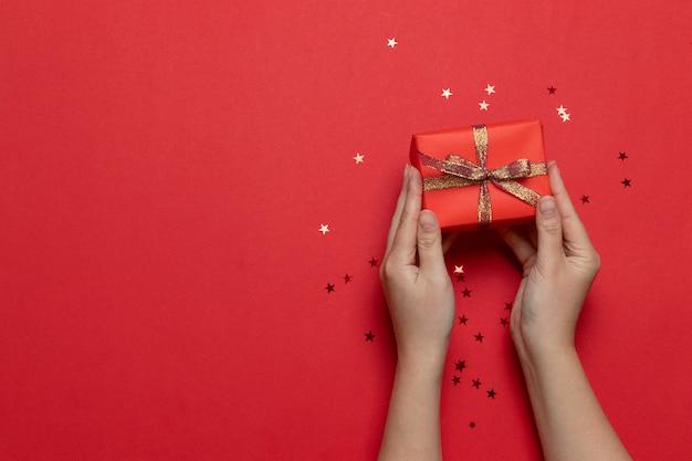 Flache lage von den frauenhänden, die die überraschungsgeschenkbox eingewickelt und mit bogen mit goldsternen auf rotem hintergrund verziert halten. geburtstag, valentinstag, weihnachten, neujahr. flacher laienstil