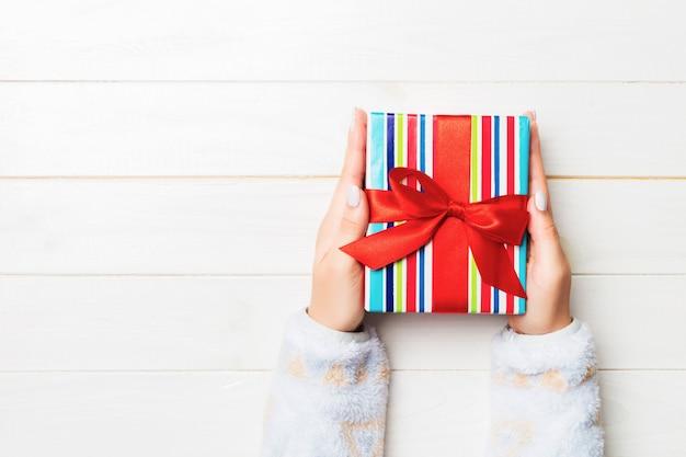Flache lage von den frauenhänden, die geschenk halten