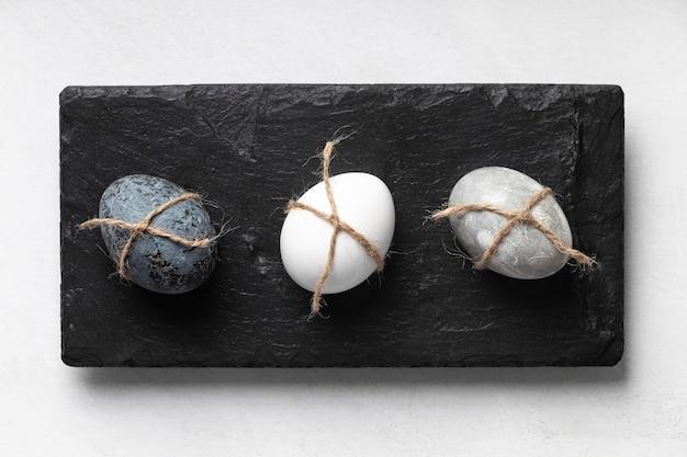 Flache lage von drei ostereiern auf schiefer
