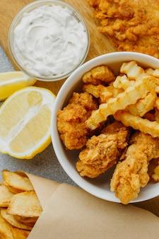 Flache lage von fish and chips in schüssel und papierumhüllung mit sauce