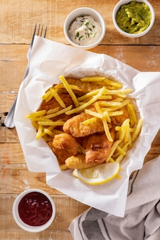 Flache lage von fish and chips mit saucen